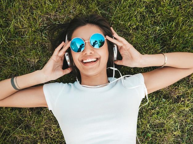 Фасонируйте портрет молодой стильной женщины битника лежа на траве в парке. девушка носит ультрамодное обмундирование. улыбчивая модель наслаждается ее выходными. женщина слушает музыку через наушники. вид сверху Бесплатные Фотографии