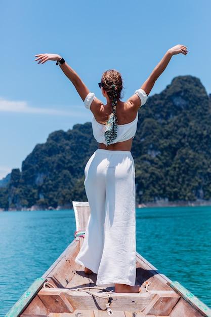 흰색 상단과 휴가, 태국 나무 보트 항해에 바지에 젊은 여자의 패션 초상화. 여행 개념. 카오 속 국립 공원의 여성. 무료 사진