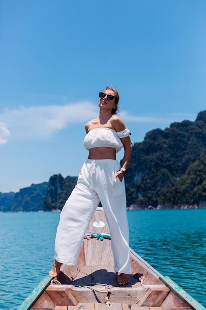 Фасонируйте портрет молодой женщины в белой верхней части и штанах на отдыхе, на тайской деревянной лодке плавания. концепция путешествия. самка в национальном парке као сок. Бесплатные Фотографии
