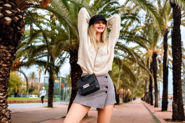 산책로에서 젊은 여자 착용, 모자, 가죽 재킷, 크로스 바디 백, 미니 스커트, 스웨터 및 트렌디 한 액세서리의 패션 초상화 무료 사진