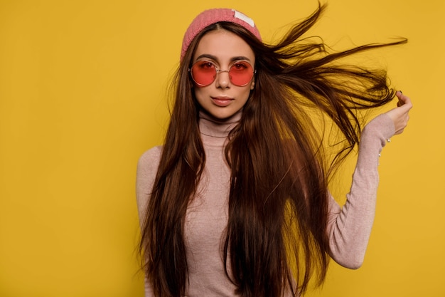 Fashion portrait of showy girl with flying hair wearing round pink glasses and cap Free Photo