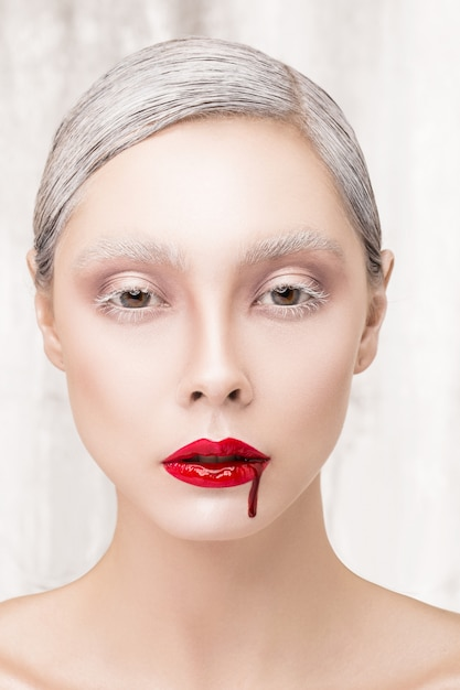 Fashion portrait of a vampire girl with blood. contact lenses Premium Photo