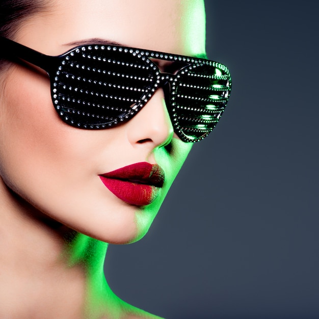 Fashion portrait of  woman wearing black sunglasses with diamonds. saturated colors Free Photo
