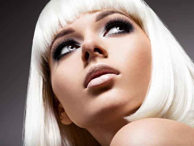 Moda ritratto di giovane bella donna con i capelli bianchi e il trucco nero dell'occhio Foto Gratuite