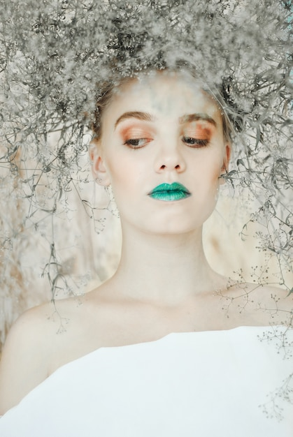 Fashion portrait of young blond woman .beautiful woman with green lips. concept of mother nature Premium Photo