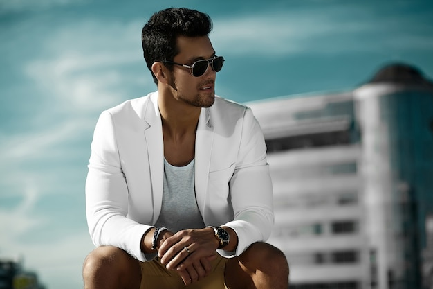 Fashion portrait of young sexy businessman handsome  model man in casual cloth suit in sunglasses sitting  in the street behind blue sky Free Photo