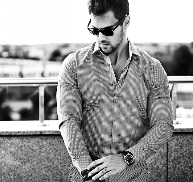 Fashion portrait of young sexy handsome model man in casual clothes in sunglasses in the street Free Photo