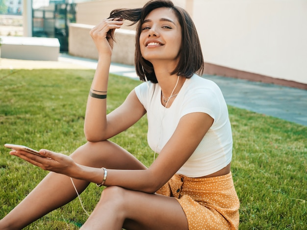 Fashion portrait of young stylish hipster woman.girl wearing cute trendy outfit.smiling model enjoy her weekends,sitting in the park. female listening to music via headphones Free Photo