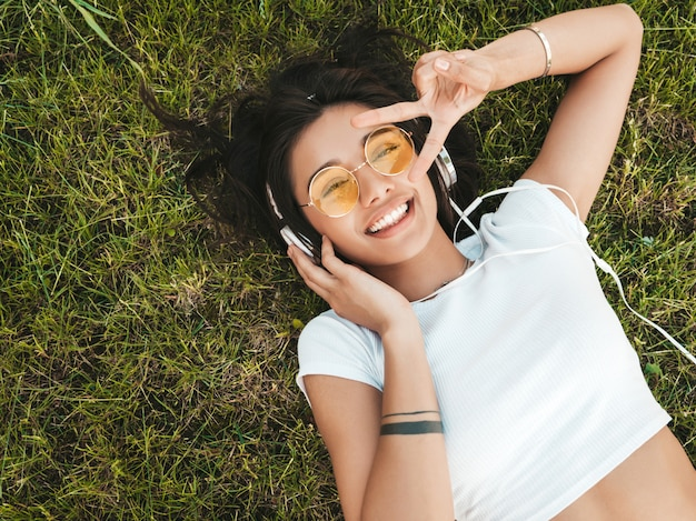 Fashion portrait of young stylish hipster woman lying on the grass in the park .girl weares trendy outfit.smiling model enjoy her weekends. female listening to music via headphones.top view Free Photo