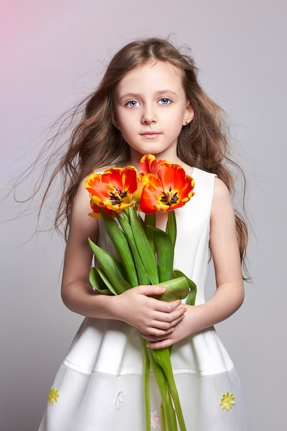 Fashion red-haired girl with tulips in hands. studio photo on light coloured background. birthday, holiday, mother's day, first day of school Premium Photo