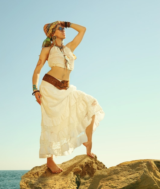Fashion shot of a beautiful boho style woman standing on a rock near sea. boho outfit, hippie, indie style Premium Photo