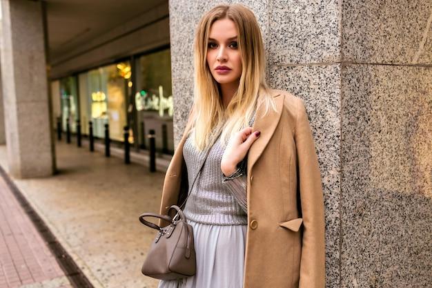金髪のエレガントな女性のファッションストリートスタイルの写真。豪華なシルクのドレス、トレンディなセーター、カシミアコート、革のバッグ、柔らかな暖色、春秋のミッドシーズン気分を身に着けています。 無料写真
