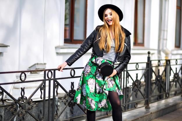 Модный уличный портрет красивой женщины с удивительными длинными светлыми волосами, стильной милой одеждой, длинной винтажной юбкой, элегантной шляпой и байкерской курткой, центром европейского города, стильной путешественницей, моделью. Бесплатные Фотографии