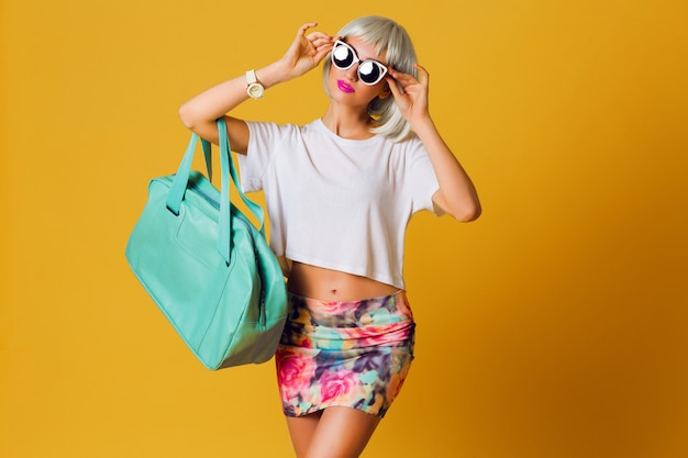 Fashion studio portrait  unusual pretty blonde girl in short party wig , white top and sexy skirt posing indoor on yellow background . sunny positive  emotions, stylish sunglasses. Free Photo
