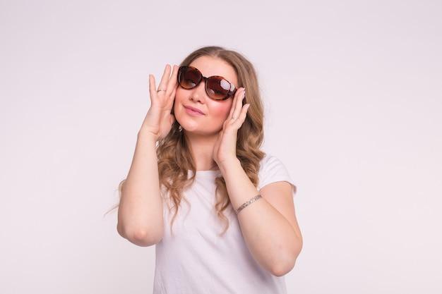 ファッション、スタイル、人々のコンセプト-白い表面にサングラスをかけている魅力的な若い女性 Premium写真