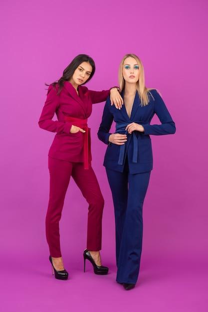 Модный стиль две улыбающиеся привлекательные женщины на фиолетовой стене в стильных красочных вечерних костюмах фиолетового и синего цвета, весенняя модная тенденция Бесплатные Фотографии