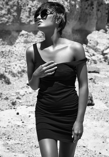 Fashion stylish beautiful young brunette woman model in summer blue dress posing near sand rocks Free Photo
