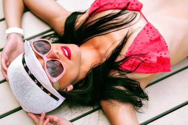 Moda ritratto all'aperto estivo di donna bruna abbronzata sottile sexy, indossando mini bikini, cappello alla moda e occhiali da sole, posa e relax in hotel di lusso, vacanza in paese tropicale. Foto Gratuite