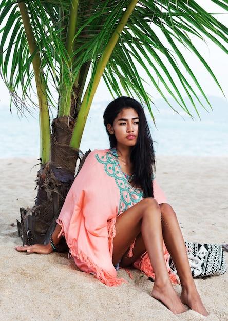 Adatti il ritratto di estate di giovane bello modello asiatico che si rilassa sulla spiaggia tropicale, indossando abiti alla moda boho, seduto sulla sabbia bianca vicino alla palma. Foto Gratuite