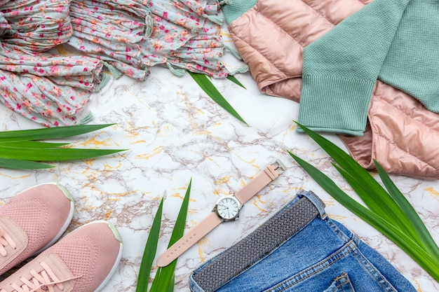 Fashion women's clothes, tropical leaves, trendy accessories set on marble background. Premium Photo