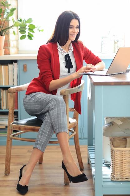 Moda giovane donna bruna che lavora da casa con il computer portatile. concetto di telelavoro Foto Gratuite