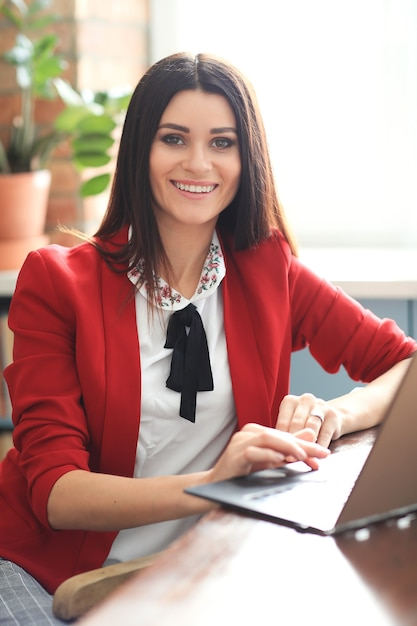 Fashion young brunette woman working from home with laptop. teleworking concept Free Photo