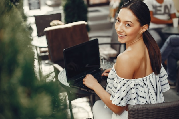 Fashion young girl sitting in a summer cafe Free Photo