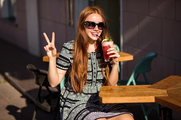 おいしい甘い夏のカクテルレモネードを保持し、長い髪と素晴らしい笑顔を持つファッションの若い女性 無料写真
