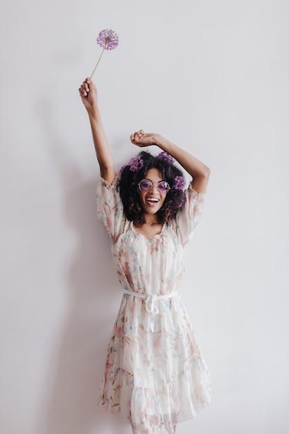 手を上げてポーズをとるファッショナブルなアフリカの女の子。家で楽しんでいるエレガントな黒人女性の肖像画。 無料写真