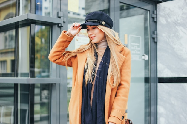 Fashionable beautiful long hair blonde girl in brown coat and blue cap at city, street style Premium Photo