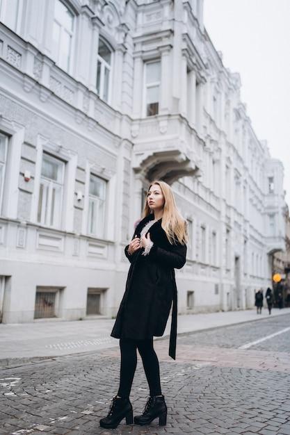 おしゃれな美しい若いブロンディ女性がトレンディなおしゃれなコートを屋外でポーズします。美容、ファッション、モデリングのコンセプト Premium写真