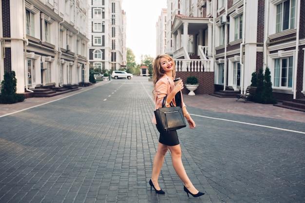 Модная блондинка с длинными волосами, идущая в черном платье по британскому кварталу. она держит кофе Бесплатные Фотографии