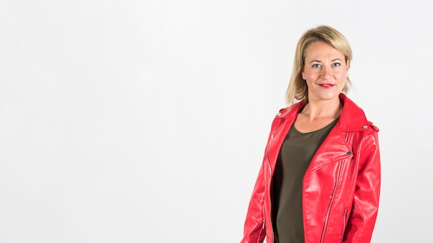 Fashionable blonde mature woman in red leather jacket against white background Free Photo
