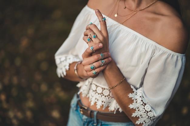 ファッショナブルな自由ho放に生きるシックな女性、白い短いブラウスとシルバーターコイズジュエリー Premium写真