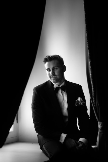 The fashionable bridegroom expects the bride near the window. black and white portrait of the groom in a black suit Premium Photo