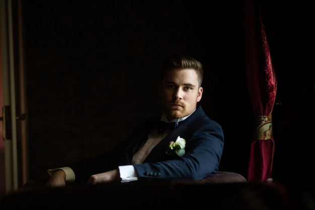 The fashionable bridegroom expects the bride near the window. portrait of the groom in a black suit Premium Photo