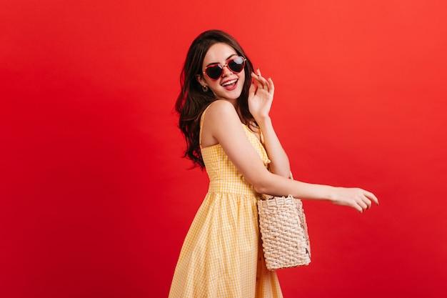 빨간 벽에 웃 고 체크 무늬 드레스에서 유행 매력적인 소녀. 하트 모양의 안경과 고리 버들 가방을 착용하는 여성 모델의 사진. 무료 사진