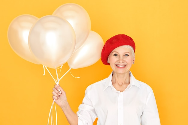 흰 셔츠와 헬륨 풍선을 들고 웃고, 기념일이나 생일을 축하하고, 행복한 표정을 짓는 빨간 모자에 유행 쾌활한 유럽 여성 연금 수령자 무료 사진