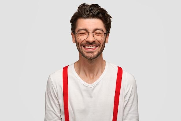 Hipster uomo allegro alla moda con un sorriso a trentadue denti, chiude gli occhi dalle risate Foto Gratuite