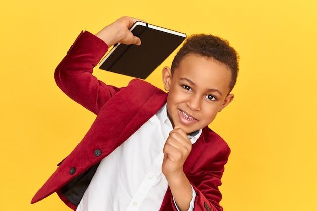 メモ帳を持っている赤いブレザーでファッショナブルな子供 無料写真