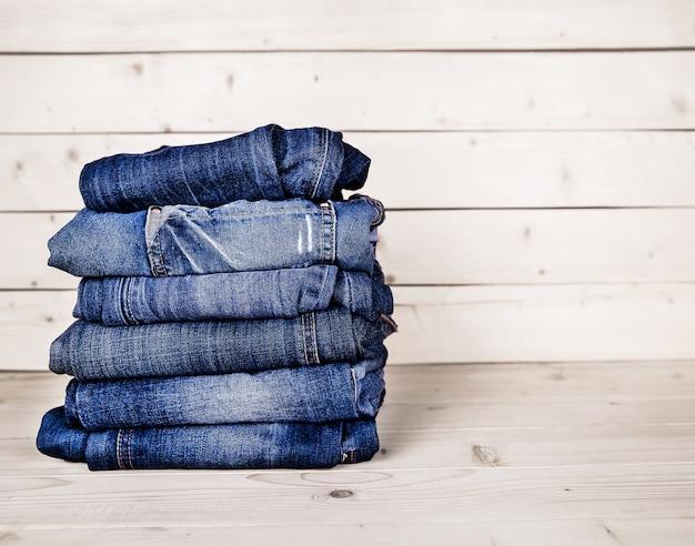 おしゃれな服。木製の背景にジーンズの山 Premium写真