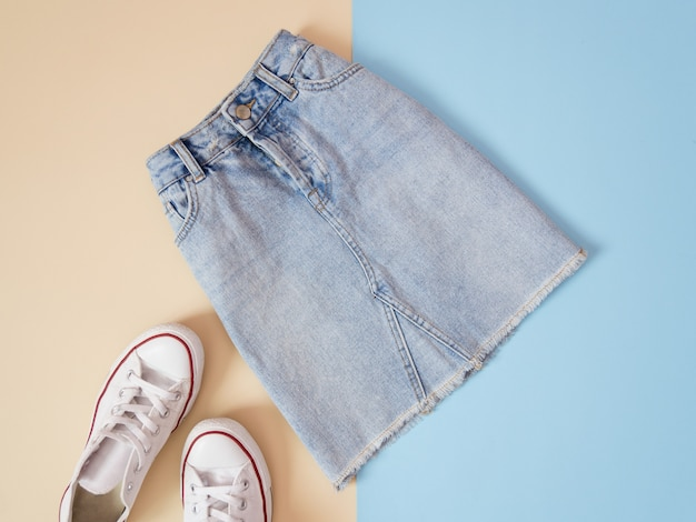 Fashionable concept. female urban style. denim skirt and white sneakers on a pale blue background, beige Premium Photo