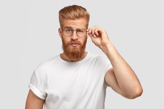 Модный крутой молодой человек с густой бородой, моргает глазами, носит круглые очки Бесплатные Фотографии