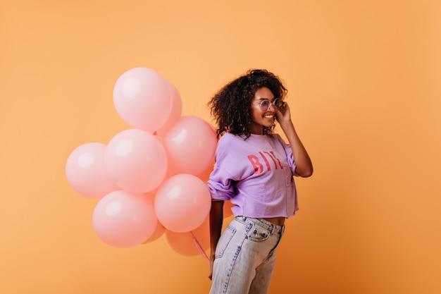 핑크 헬륨 풍선을 들고 웃 고 안경에 유행 곱슬 여자. 오렌지에 격리 기쁘게 아프리카 생일 소녀입니다. 무료 사진