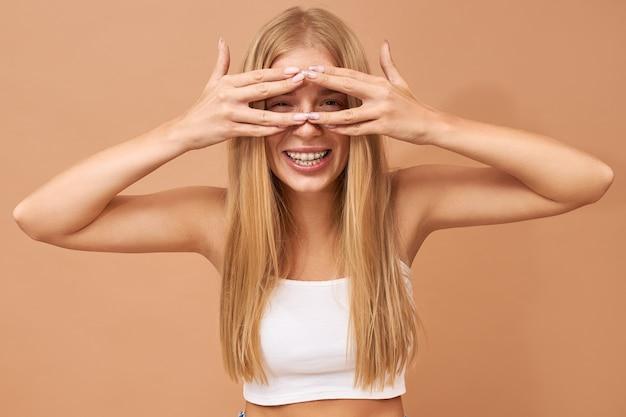 Модная милая девочка-подросток со светлыми волосами носит джинсы и белый топ Бесплатные Фотографии