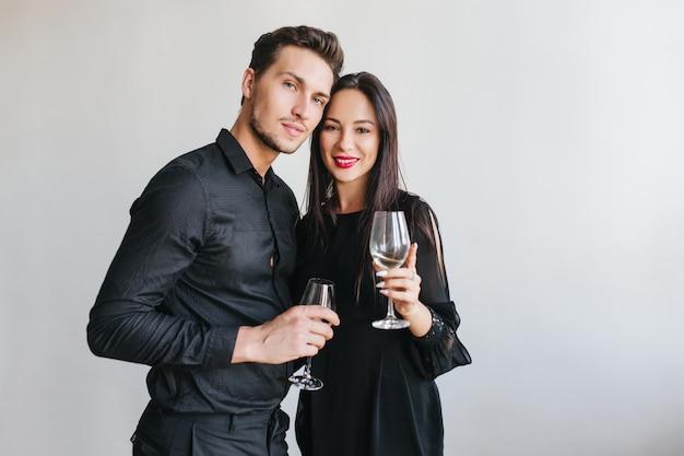 Модная темноволосая дама с нежной улыбкой склоняется к мужу, позируя на вечеринке Бесплатные Фотографии