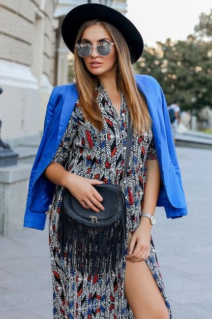 ヨーロッパでの休暇中に歩くエレガントな秋の服のファッショナブルな女の子。スタイリッシュなレザーバッグ。青いジャケットと黒い帽子。 無料写真