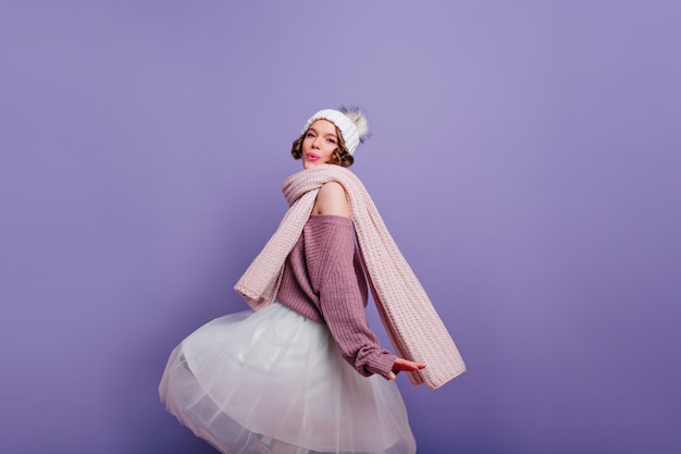 Модная девушка в длинном шарфе развлекается на фотосессии в помещении. очаровательная дама в пышной юбке и вязаной шапке танцует на фиолетовой стене. Бесплатные Фотографии