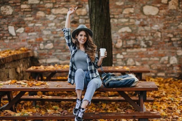 Модная девушка в коротких синих джинсах сидит с чашкой кофе перед старым зданием Бесплатные Фотографии