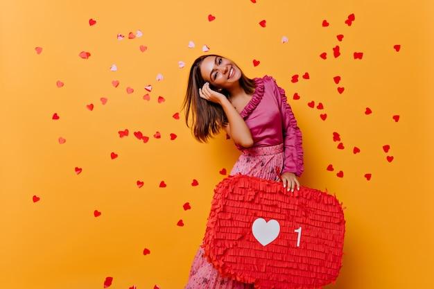소셜 네트워크를 즐기는 스트레이트 머리를 가진 유행 소녀. 오렌지에 고립 된 황홀 할 정도로 웃는 여자의 실내 초상화. 무료 사진